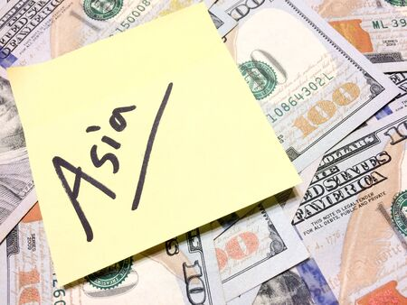 American cash money and yellow sticky note with text Asia in black color aerial view Imagens