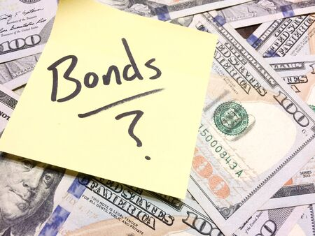 American cash money and yellow post it note with text Bonds with question mark in black color aerial view