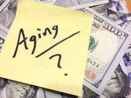 American cash money and yellow paper note with text Aging with question mark in black color aerial view