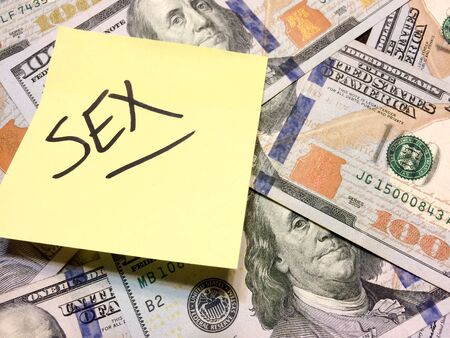 American cash money and yellow post it note with text Sex in black color aerial view