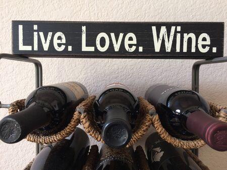 Wine bottles Live Love Wine on rack Standard-Bild