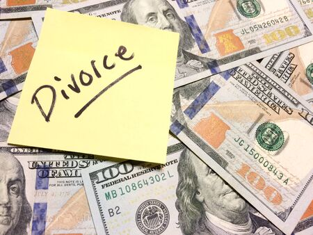 American cash money and yellow post it note with text Divorce in black color aerial view