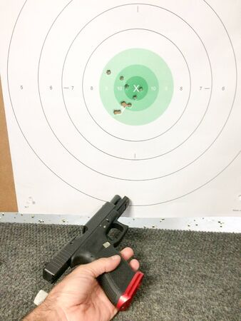 Fireams training pistol and bullet holes with hand