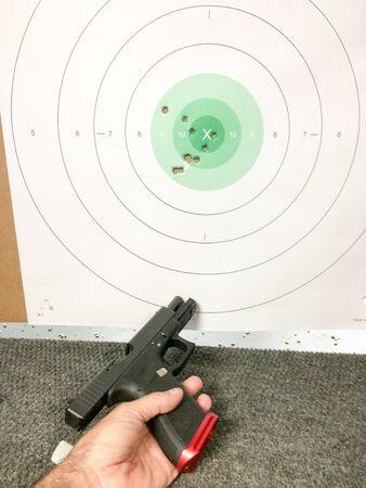 Pistola de entrenamiento Fireams y agujeros de bala con la mano