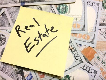 American cash money and yellow sticky note with text Real Estate in black color aerial view
