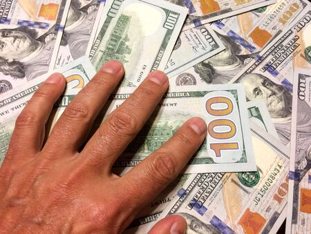 American dollar bills with hand on money with gold number 100