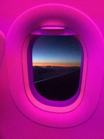 Oval Airplane cabin window with pink light glow 免版税图像 - 139513542