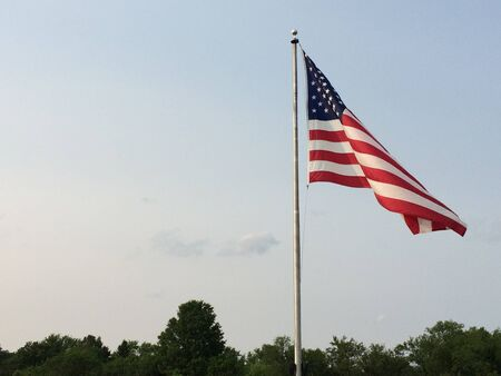 american flag big waving in wind with sky