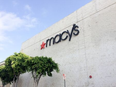 Macys sign on building outdoors at shopping mall with blue sky