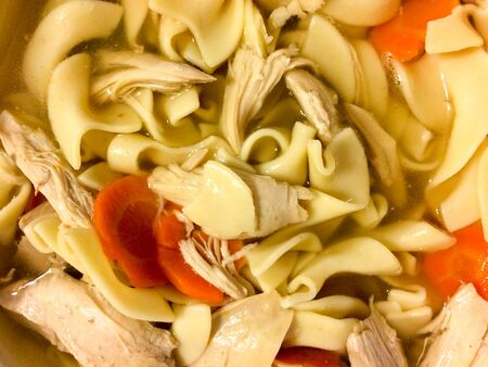 Chicken noodle soup overhaed view with carrot on homestyle floral table cloth Stok Fotoğraf