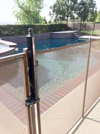 Safety fence at swimmimg pool with child protection gate for drowning