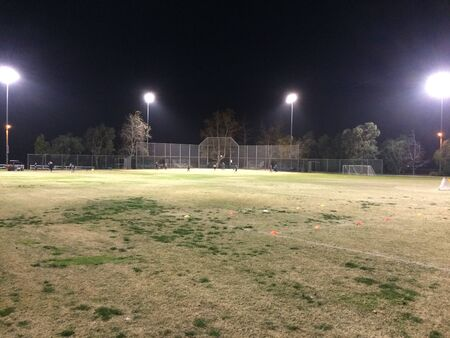 Night time baseball game at playing field outdoor with people and kids