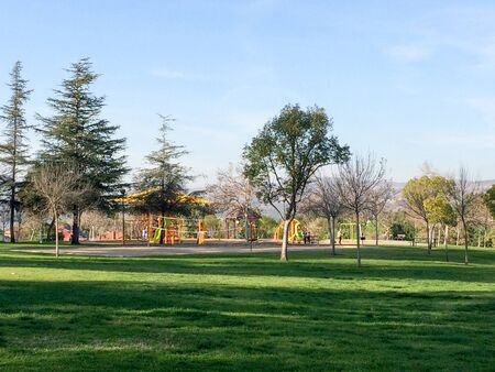 playground at park with green grass lawn and trees