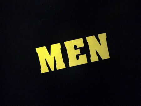 yellow sign men text restroom on black background