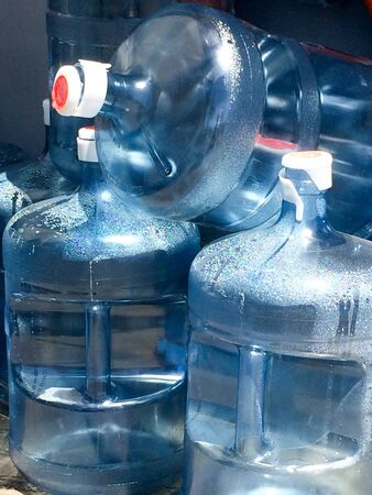 Five 5 gallon water bottles full and empty blue plastic dry and condensation droplets on USS Iowa naval warship destroyer battleship