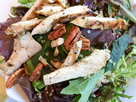 Gourmet walnut mixed greens salad with chicken close up on table
