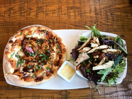 Gourmet bbq barbecue chicken sauce pizza bread and mixed poultry salad on plate on table Banque d'images