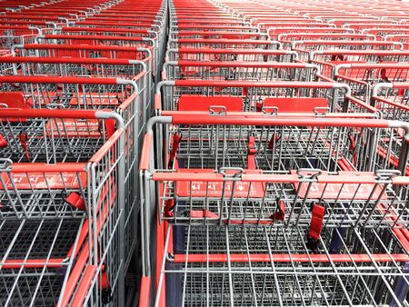 red and silver metal shopping carts organized in mass rows making square patterns Imagens
