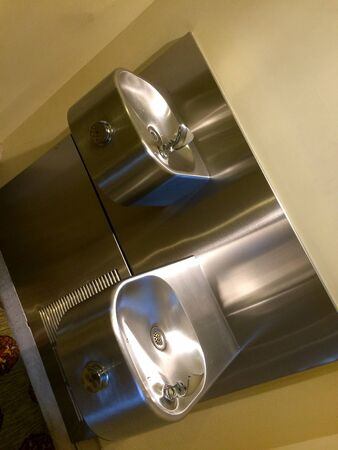 Public water fountain of stainless steel shiny clean refreshing silver reflections