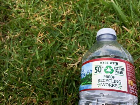 Plastic water bottle close up on green grass nature environment concept for recycling