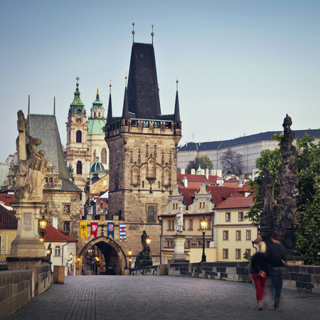 st charles: View of the Lesser Bridge Tower of Charles Bridge in Prague Karluv Most the Czech Republic. Couple walking in the morning.