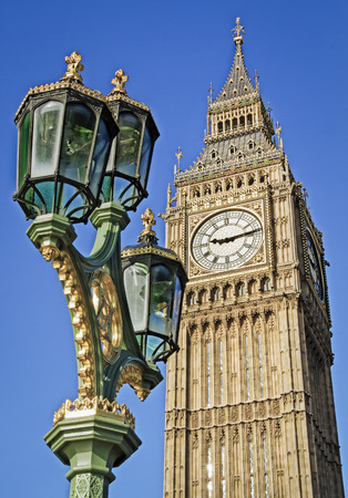 typically english: Big Ben seen from Westminster Bridge with an ornate lamp post in the foreground. Clear summer sky.