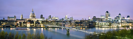 Panoramisch beeld van St. Paul's Cathedral, Millennium Bridge en het Financial District in de schemering.