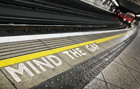 typically english: London tube platform edge. Painted warning on the floor. Train approaching.