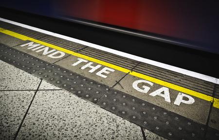 typically english: London tube platform edge. Painted warning on the floor.