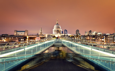 Millennium Bridge leads to Saint Pauls Cathedral in central London at night Stock Photo