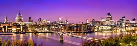 Panorama van Londen: St. Paul's Cathedral, Millennium Bridge en het Financial District in de schemering.