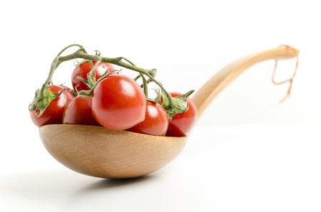 cherry tomatoes on wooden spoon on white background photo