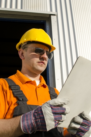 worker with helmet and sunglasses in front of industrial hall photo