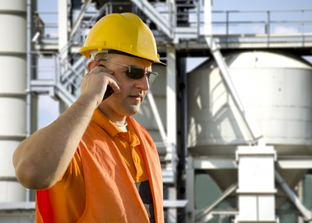 gas plant: worker with helmet and sunglasses talking on mobile phone in front of oil plant Stock Photo