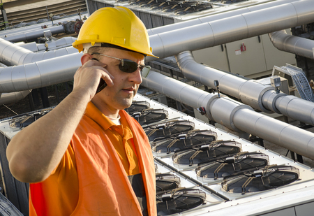 worker with helmet and sunglasses talking on mobile phone in front of cooling plant photo