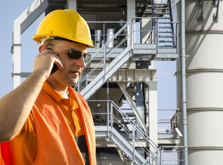 worker with helmet and sunglasses talking on mobile phone in front of industrial plant photo