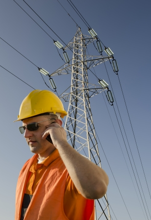 worker with helmet and sunglasses talking on mobile phone in front of transmission tower photo