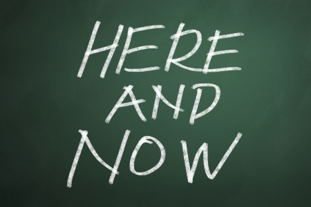 backgruond: Here and now words on chalkboard backgruond Stock Photo