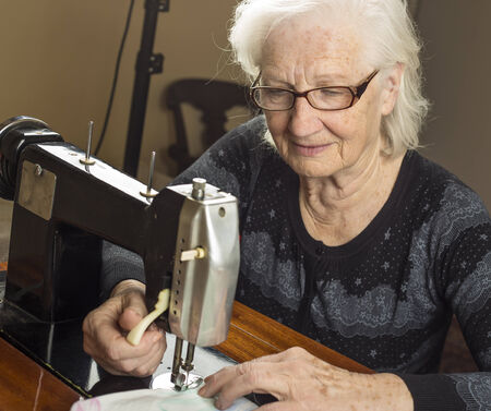 Older woman working on sewing machine  photo