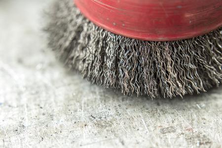 circular wire brush on workbench close up photo