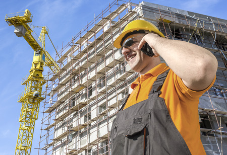 worker in front of construction site talking on smart phone photo