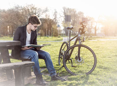 teenager with bicycle reading book in park photo