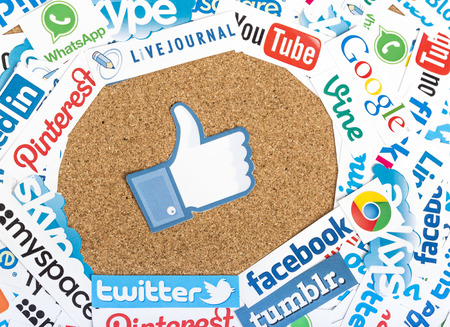 BELGRADE - JUNE 17, 2014 Social media website logos Facebook Twitter and other printed on paper with like icon on cork bulletin board
