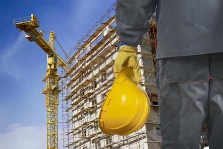 werknemer met helm in de voorkant van de bouw steigers en bouwkraan Stockfoto