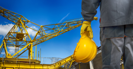 worker with helmet in front of scaffolding and construction crane photo