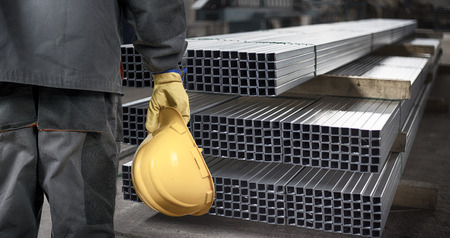 siderurgia: trabajador con casco en nave de producción frente a los perfiles de chapa de acero Foto de archivo