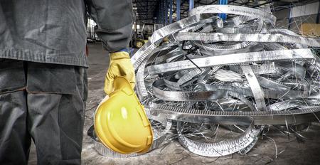 metal scrap: worker with helmet in production hall in front of steel sheet metal scrap