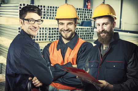 steel sheet: smiling workers in protective uniforms and protective helmet in production hall in front of steel sheet metal profiles Stock Photo