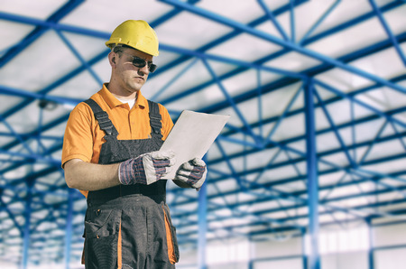 engineering clipboard: Worker in protective uniform in production hall Stock Photo