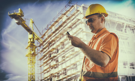 engineering clipboard: worker with protective uniform in front of construction scaffolding and construction crane